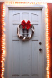 Christmas lights and wreath on front door at night Stock Image
