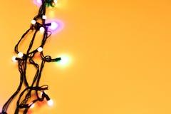 Christmas lights on yellow background stock photos
