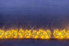 Christmas lights yellow stars burn on dark ultramarine wooden background. New Year festive home interior Royalty Free Stock Photo