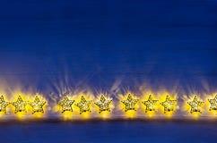 Christmas lights yellow stars burn on dark ultramarine wooden background. New Year festive home interior Stock Image