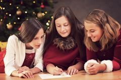 Christmas list of wishes. Girls writing a christmas list of wishes for santa royalty free stock images