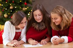Christmas list of wishes. Girls writing a christmas list of wishes for santa stock photos