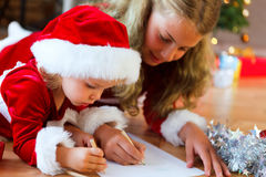 Christmas list of wishes. Siblings writing a christmas list of wishes for santa royalty free stock images