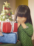 Christmas. Little asian girl covering her eyes in front of christmas gifts Stock Photography