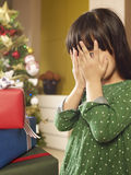 Christmas. Little asian girl covers her eyes in front of christmas gifts Stock Photo