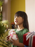 Christmas. Little asian girl holding a toy snowman and thinking in front of a christmas tree Stock Photos