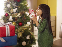 Christmas. Little asian girl kissing a toy snowman Stock Photo
