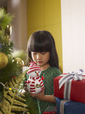 Christmas. Little asian girl talking to a toy snowman in front of a christmas tree Stock Images