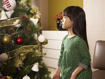 Christmas. Little asian girl thinking next to a christmas tree Royalty Free Stock Photo