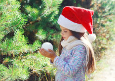 Christmas little child in santa hat with snowball Stock Photo