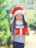 Christmas little girl child in santa hat with gift box Royalty Free Stock Photos