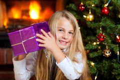 Christmas -  little girl holding gift and smiling Royalty Free Stock Photos