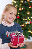Christmas -  little girl holding gift and smiling Stock Photos