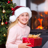 Christmas -  little girl holding gift and smiling Stock Image