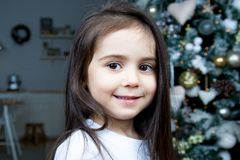 Against the Christmas tree, a portrait of a little girl. Christmas. The little girl is smiling. Behind her beautiful Christmas tree stock images