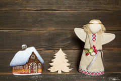Christmas little glass house with snow covered roof, christmas t. Ree and angel on dark wooden background Royalty Free Stock Photos