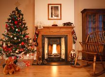 Christmas living room. Traditional living room with a cosy open fire, adorned with christmas decorations and a tree. [Note: Picture above fireplace is Stock Image