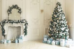 Christmas living room with a Christmas tree, fireplace, gifts and a large window. Beautiful New Year decorated classic home interi. Or stock photos