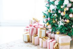 Christmas living room with a Christmas tree, gifts and a large window. Beautiful New Year decorated classic home interior.  stock photos
