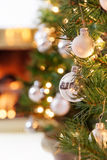 Christmas living room fire. Glittering silver and white Christmas tree decorations by a warm fire Stock Photos