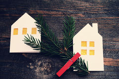 Christmas lodges from white paper with a fir-tree branch on a wooden background. Royalty Free Stock Photos