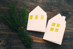 Christmas lodges from white paper with a fir-tree branch on a wooden background. Royalty Free Stock Photography