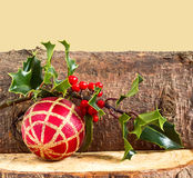 Christmas log, bauble and holly Royalty Free Stock Photography