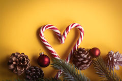 Christmas lolipop and branch. With cones on yellow background Stock Photos