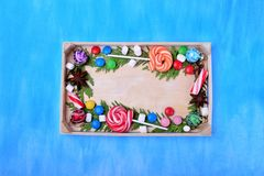 Christmas lollipops, sweets of different colours, marshmallows and thuja branches framing copy space. On a wooden tray. Festive background royalty free stock image
