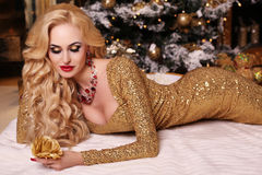 Christmas look, gorgeous woman posing in room with Christmas decorations royalty free stock photo