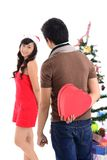 Christmas love. Vertical shot of a guy holding behind the back a heart-shaped Christmas giftbox for his girlfriend, concept of love Royalty Free Stock Photo