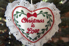 Christmas is Love. An embroidered and lace heart stating Christmas is Love royalty free stock image