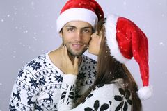 Christmas love . Beautiful woman kissing an handsome man in Santa hat. Christmas love . Beautiful women kissing an handsome men in Santa hat on a white Royalty Free Stock Photography