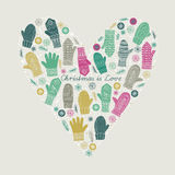 Christmas is Love. Greeting card with a fun collection of woollen winter mittens and snowflakes forming a symbolic heart shape in CMYK colours Royalty Free Stock Photo
