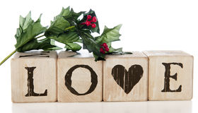 Christmas Love. A spring of Christmas holly with berries on rustic alphabet blocks arranged to spell LOVE.  On a white background Stock Image
