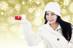 Christmas luxury gift by beautiful woman in white. A girl is giving a christmas red gift with beautiful defocused golden lights background Stock Image
