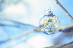 Christmas magic Ball, Waiting for Christmas, Magic Atmosphere. Transparent glass Christmas ball with light and stars in blue sky. And branch winter background royalty free stock photo