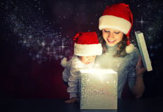 Christmas magic gift box and a happy family mother and baby