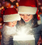 Christmas magic gift box and a happy family mother and baby. Christmas magic gift box and a women happy family mother and Child baby stock photography