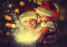 Christmas magic gift box and a happy family mother and daughter baby girl royalty free stock images