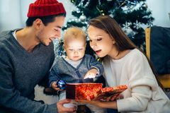 Christmas magic gift box and happy parents and Child baby Stock Images