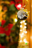 Christmas magic night with silver bauble. Celebrating the magic of Christmas night with traditional black bauble and golden ribbons. Over bokeh of defocused Royalty Free Stock Images