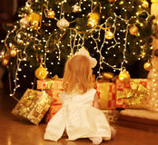 Christmas, magic, people concept - happy baby dreams. Near christmas tree with gifts stock images