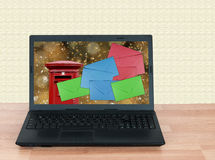 Christmas mail, email. Laptop computer on desk. UK letter box. Royalty Free Stock Photo