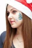 Christmas makeup. A young girl with a beautiful holiday makeup face-art Stock Photography