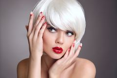 Christmas makeup and manicure nails. Surprised woman face posrtr. Ait. blonde girl with short bob white hair style and red lips posing isolated on grey studio Royalty Free Stock Images