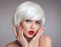 Christmas makeup and manicure nails. Surprised woman face posrtr. Ait. blonde girl with short bob white hair style and red lips posing isolated on grey studio Royalty Free Stock Photography