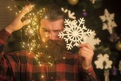 Christmas man with beard on serious face and garland. Garland on santa claus man as decoration. Party and celebration. Winter holiday and xmas. New year guy stock images