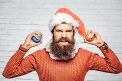 Christmas man with decorative balls. Young handsome bearded santa claus man with long beard in red sweater and new year hat holds decorative christmas or xmas Stock Photography