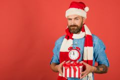 Christmas man hold alarm clock and gift box. New year, xmas holidays celebration. Time to celebrate. Boxing day concept. Hipster in santa hat, scarf on red stock photos